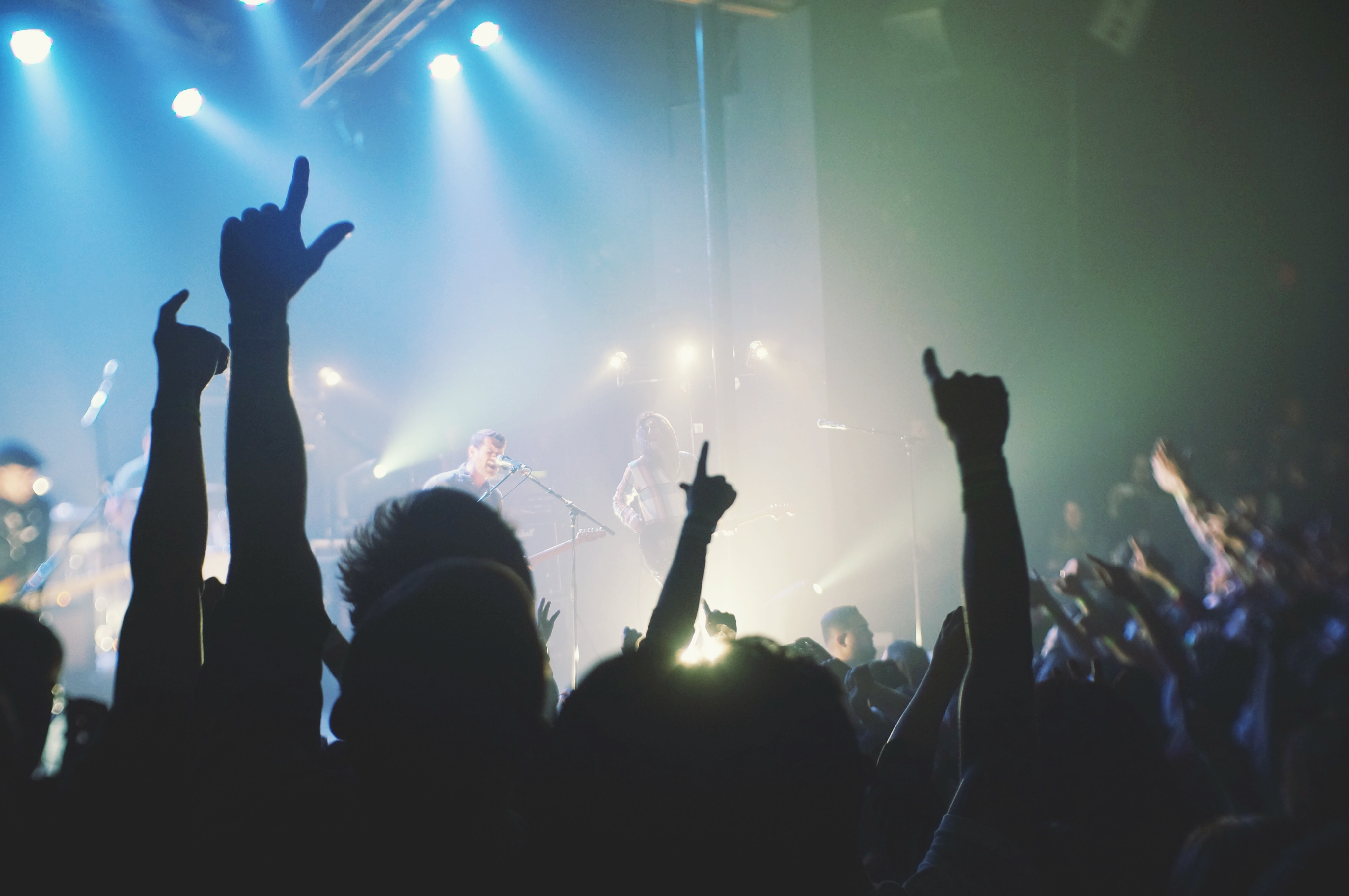 Silhouettes of concert goers lifting up their hands with a rock band performing on stage