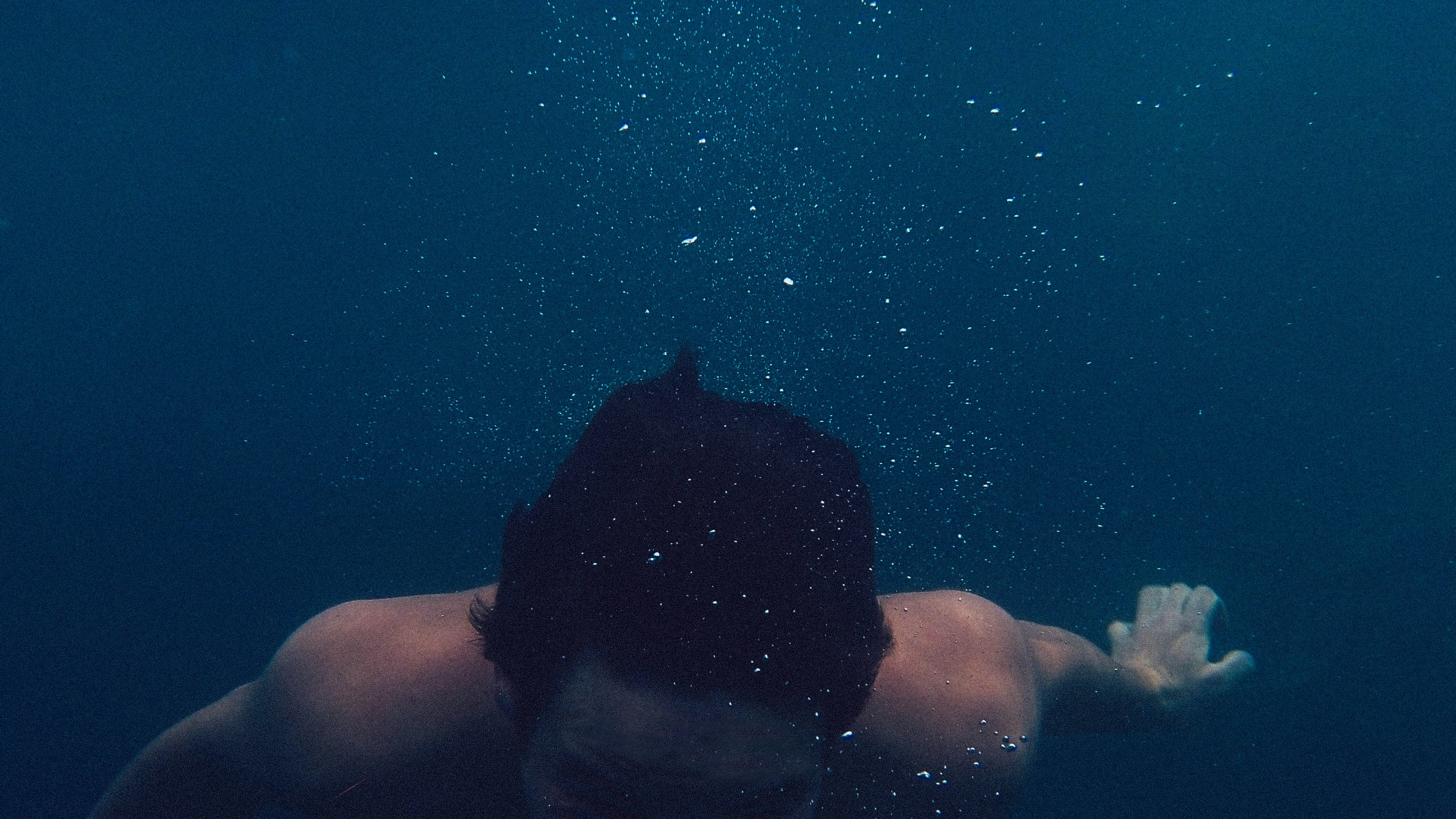 man submerged on body of water