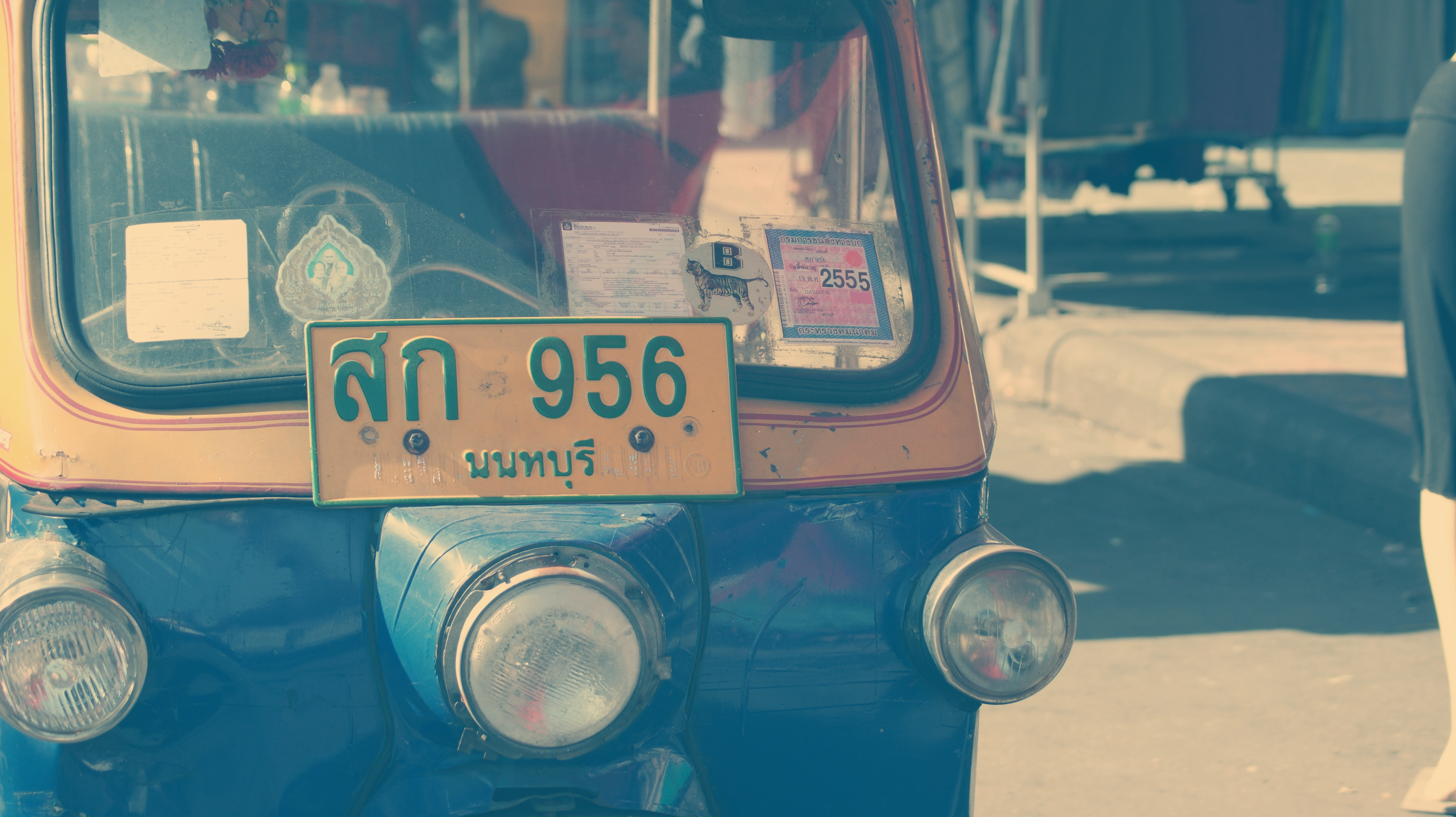 Macro view of tuk tuk taxi with front yellow license plate on street
