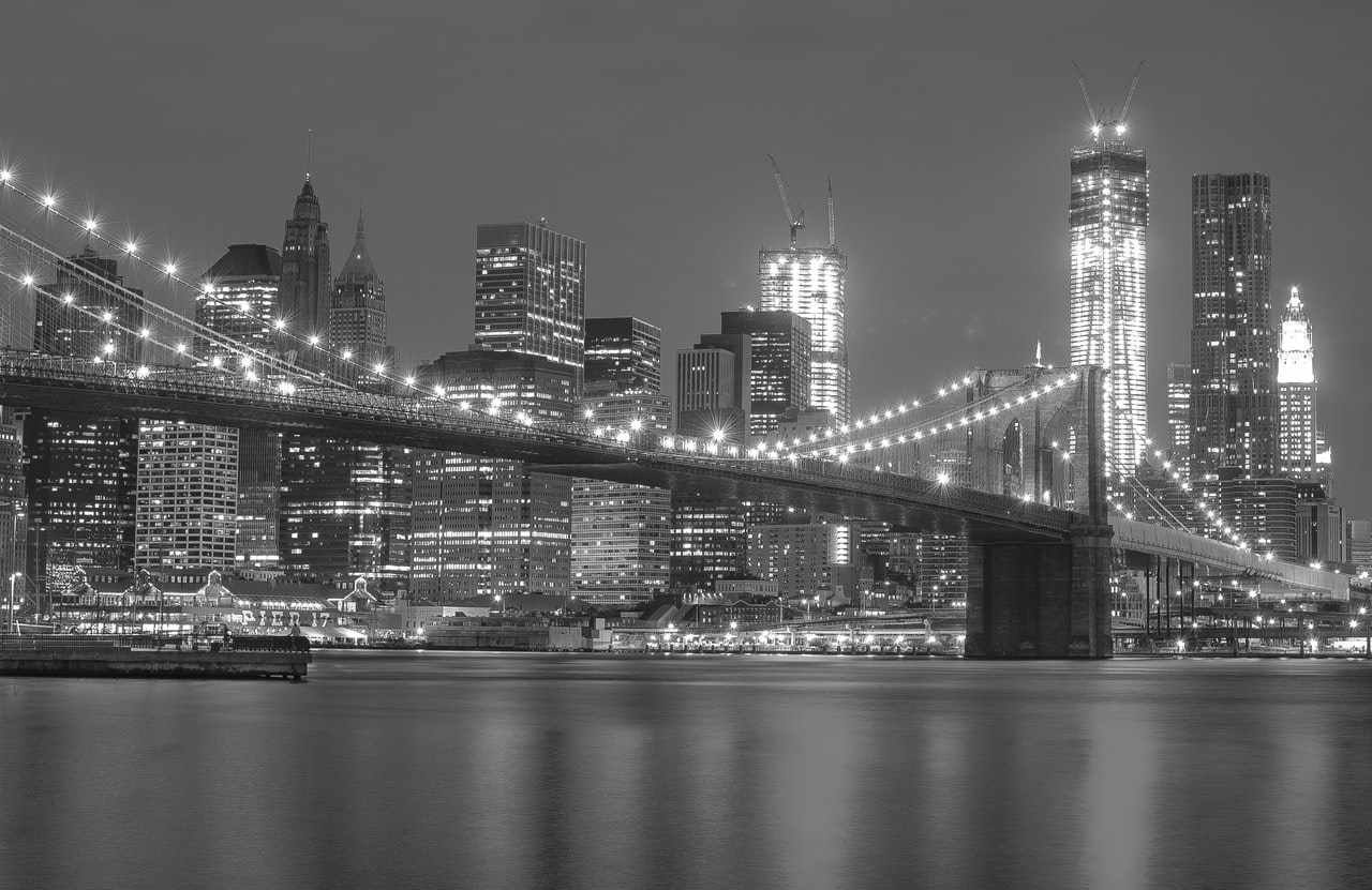 Black and white photo of the Brooklyn Bridge with the Manhattan skyline in the distance