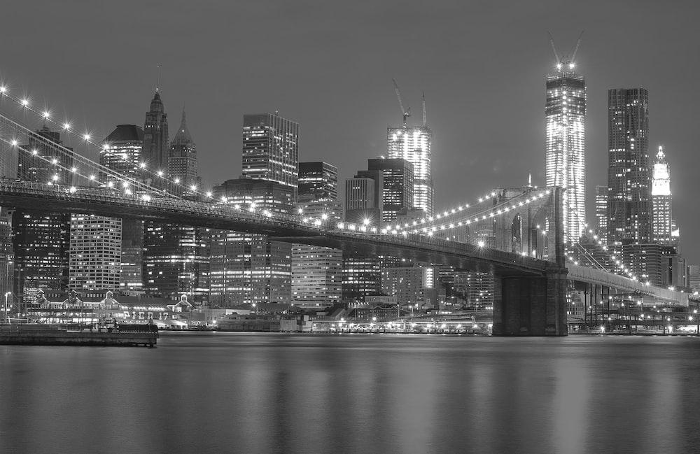 grayscale photo of lighted Brooklyn Bridge