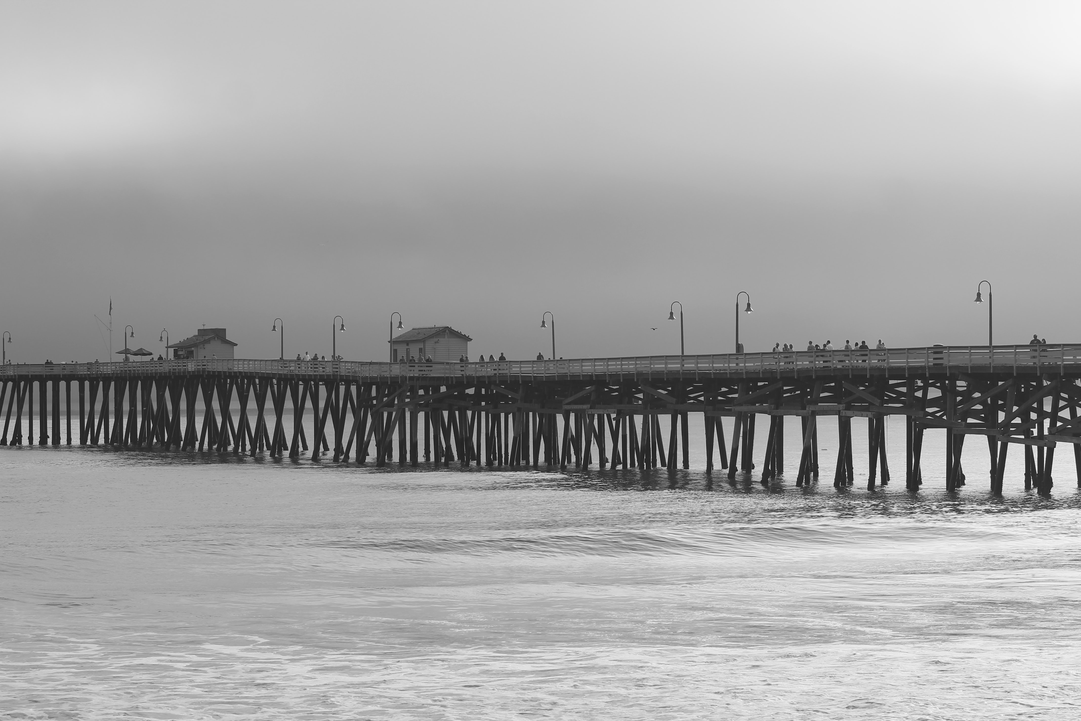 Black and white long shot of the pier and sea with grey sky