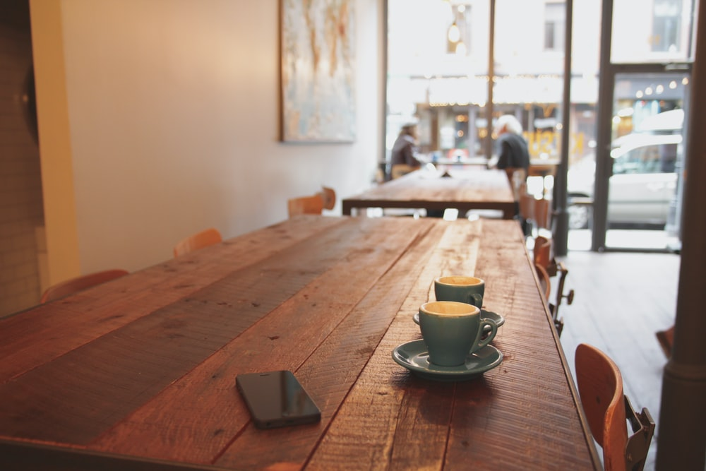 two gray ceramic mugs on brown wooden dining table