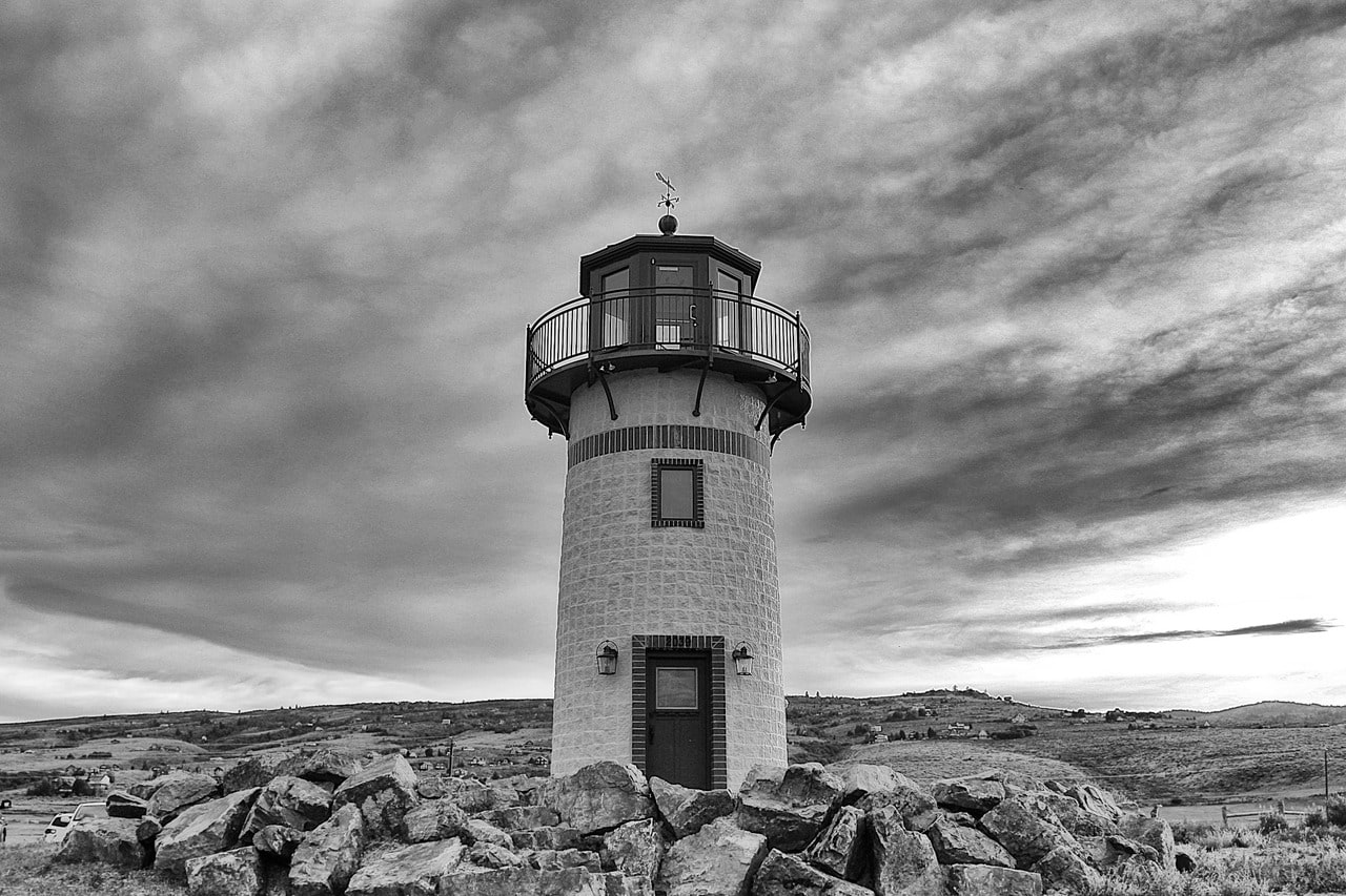 Black and white shot of traditional lighthouse near rocks with cloudy sky
