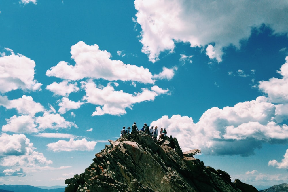 people on rock formation under white cloudy sky