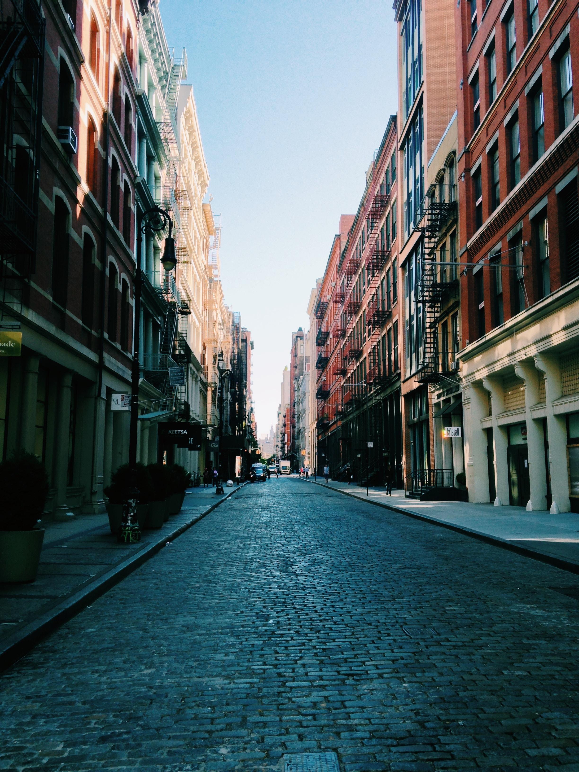 photo of road between brown buildings