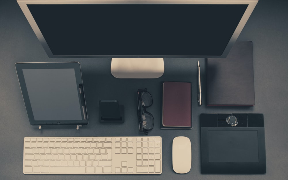 gray computer set with tablet and eyeglasses