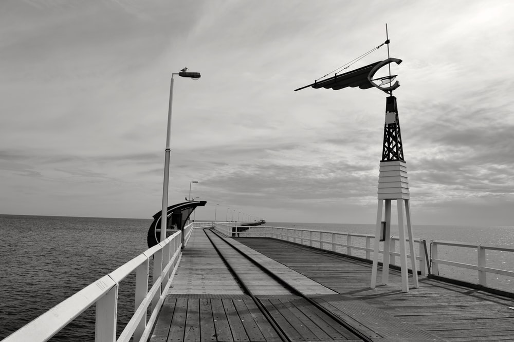 wooden wind vane on bridge near the body of water