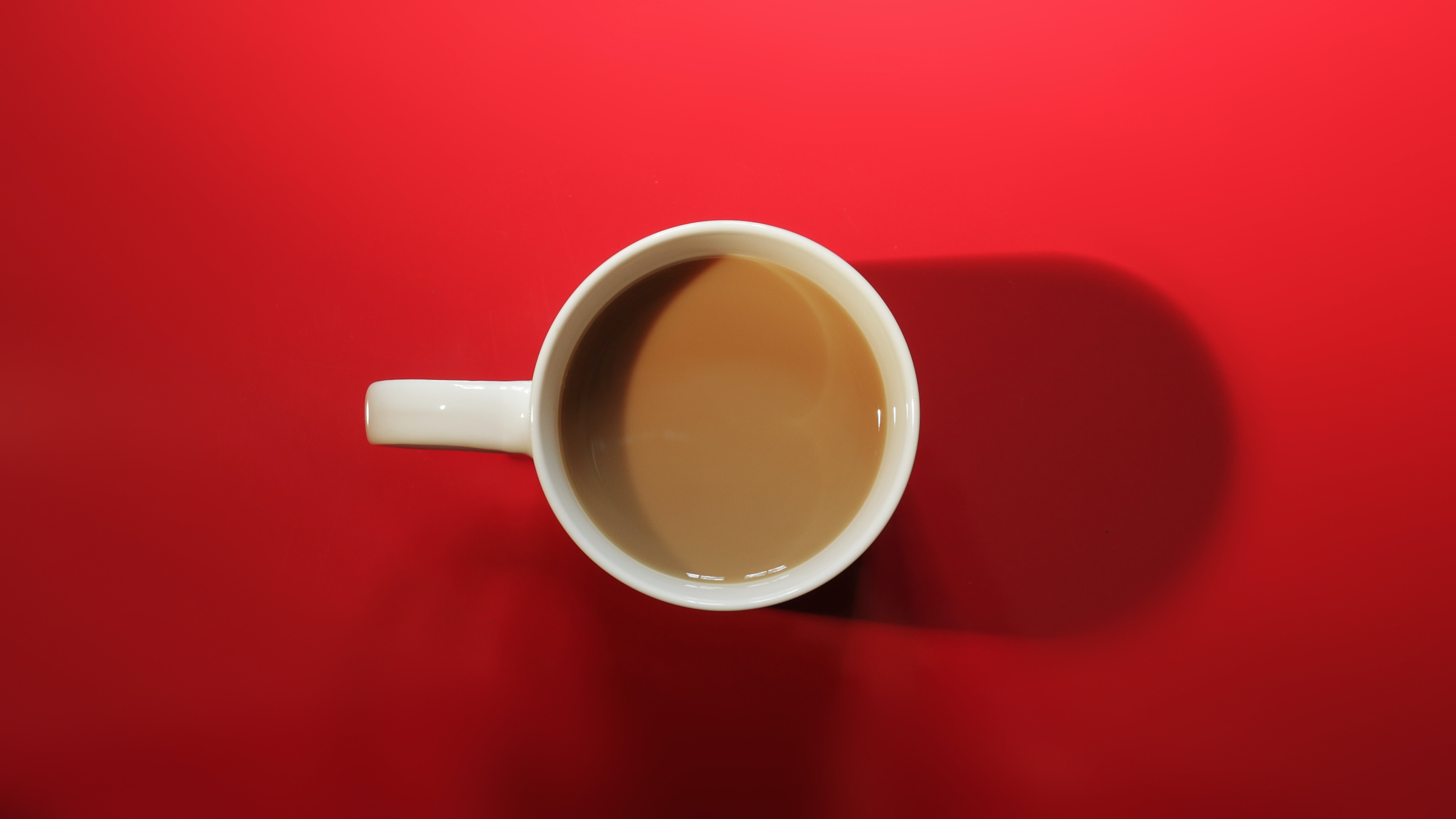 A top view of a half filled mug containing coffee in a red background