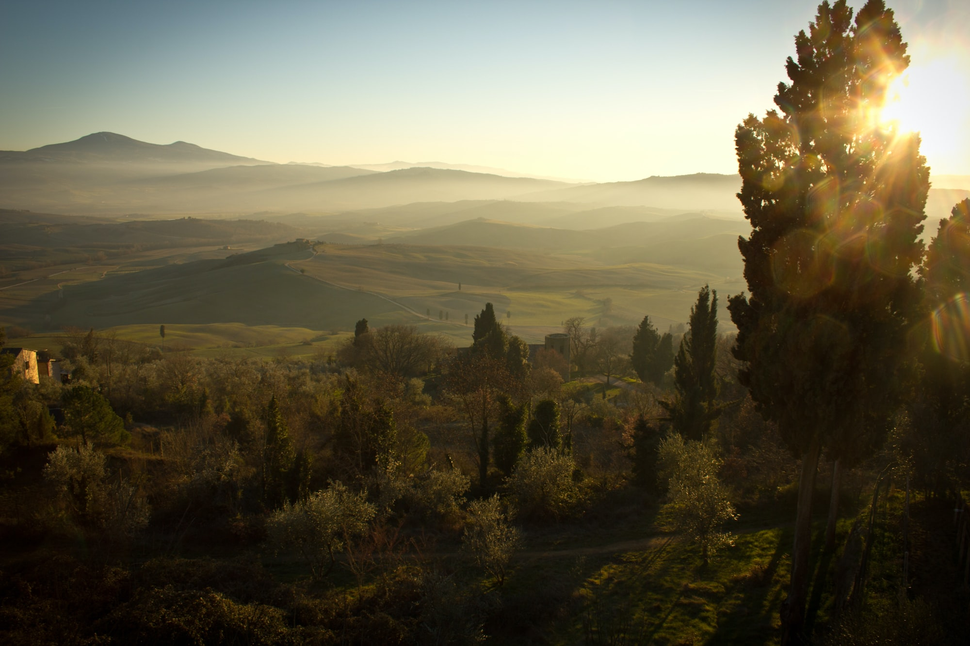 A picturesque landscape with a fertile valley under the setting sun