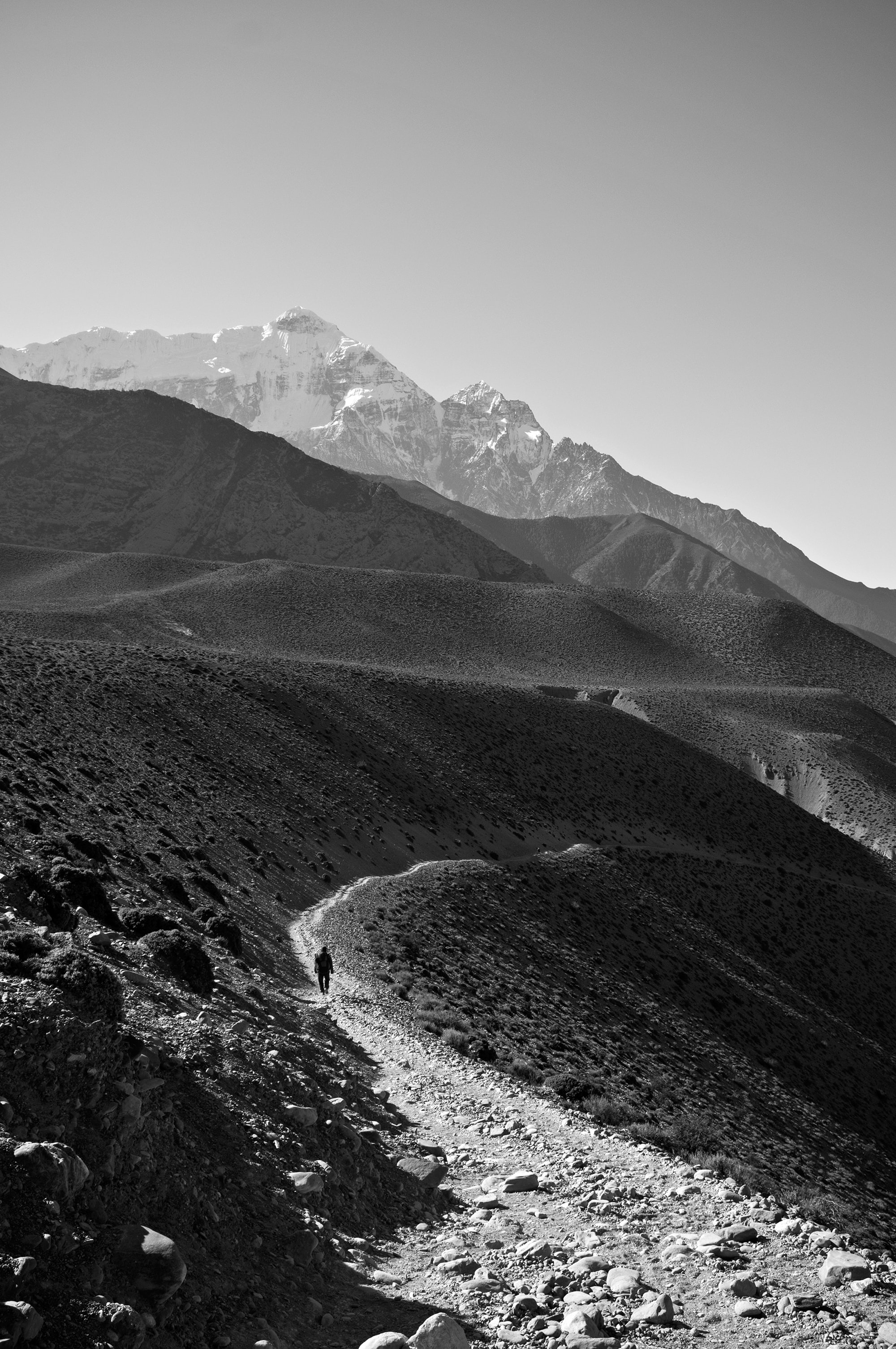 Black and white shot of person walking on desolate mountain trail with clear sky