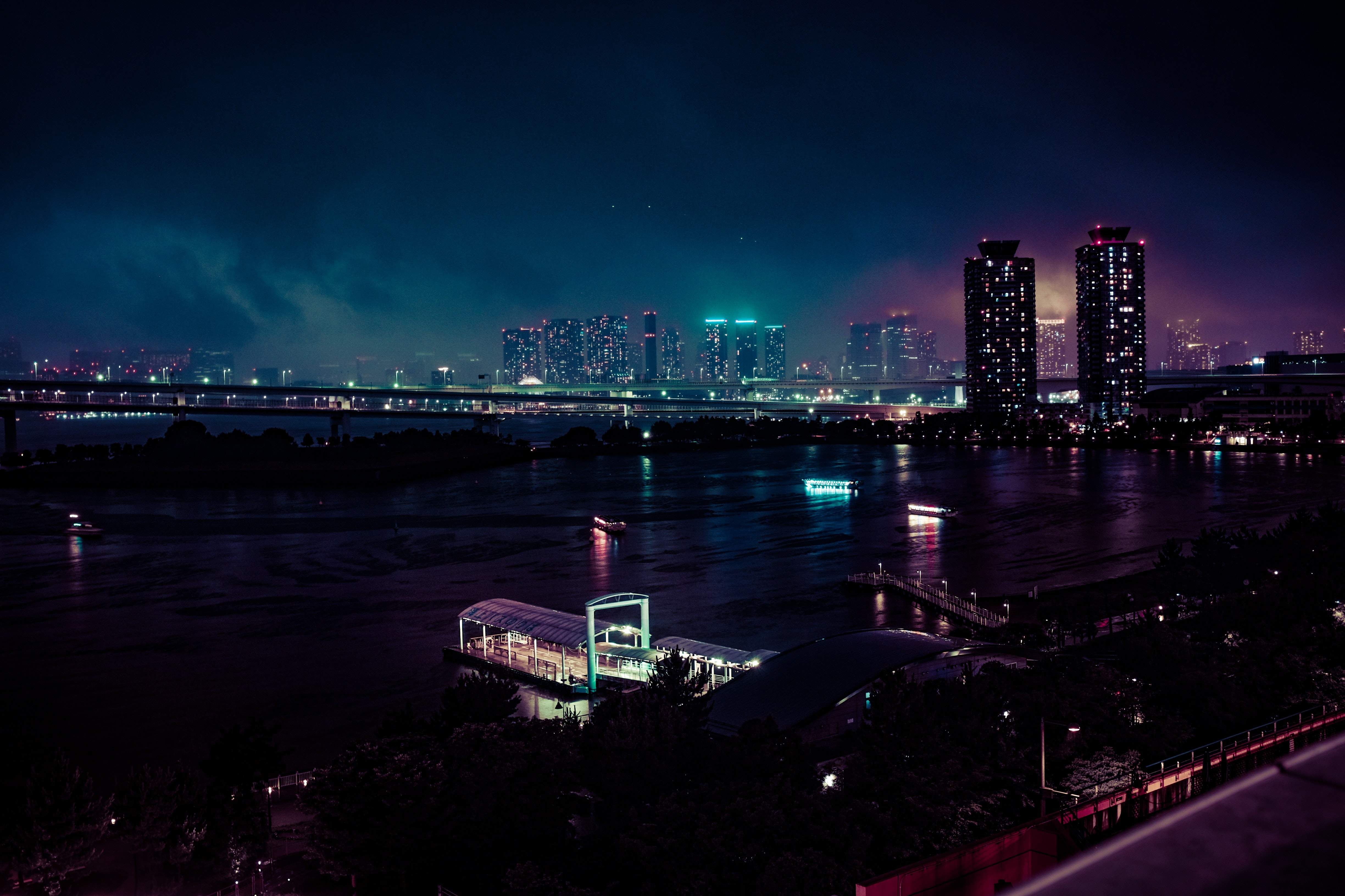 bridge above body of water near lightened buildings during night time