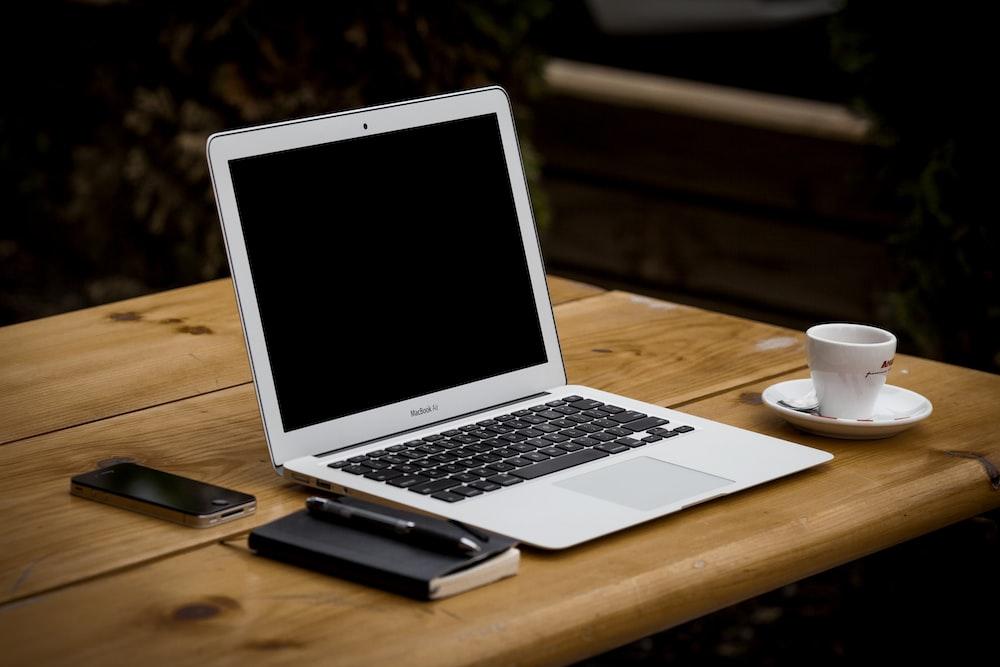MacBook Air near mug on table