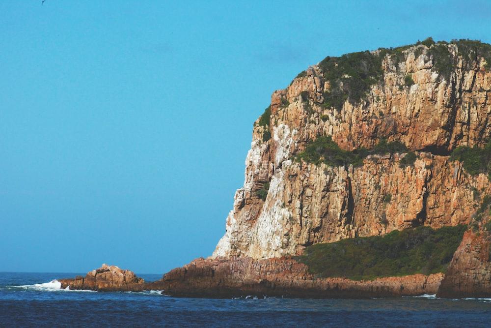 brown mountain near ocean during daytime