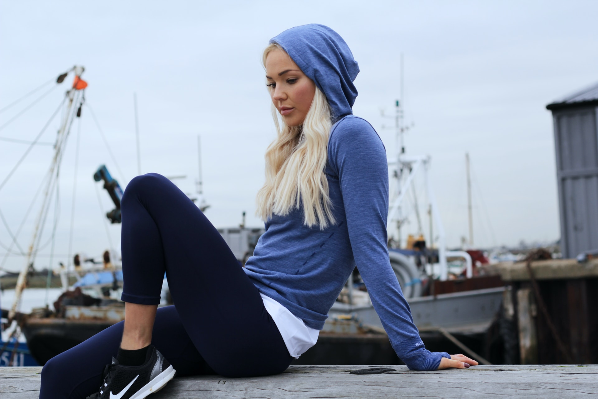 woman in blue hoodie and black leggings lounging at gray concrete surface