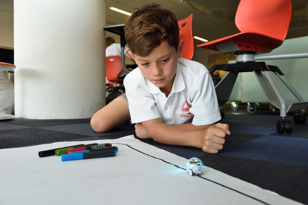 boy lying on floor with markers and white paper