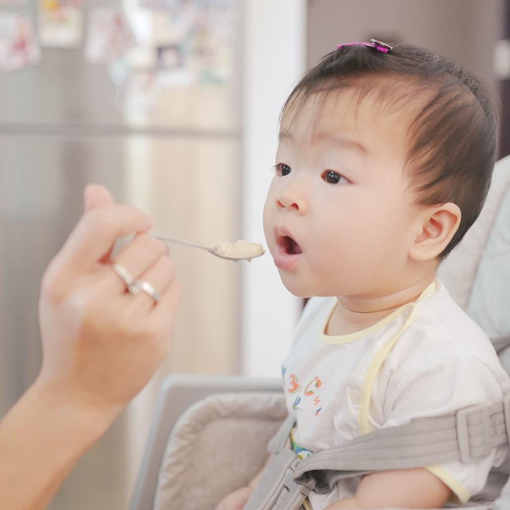 person feeding baby