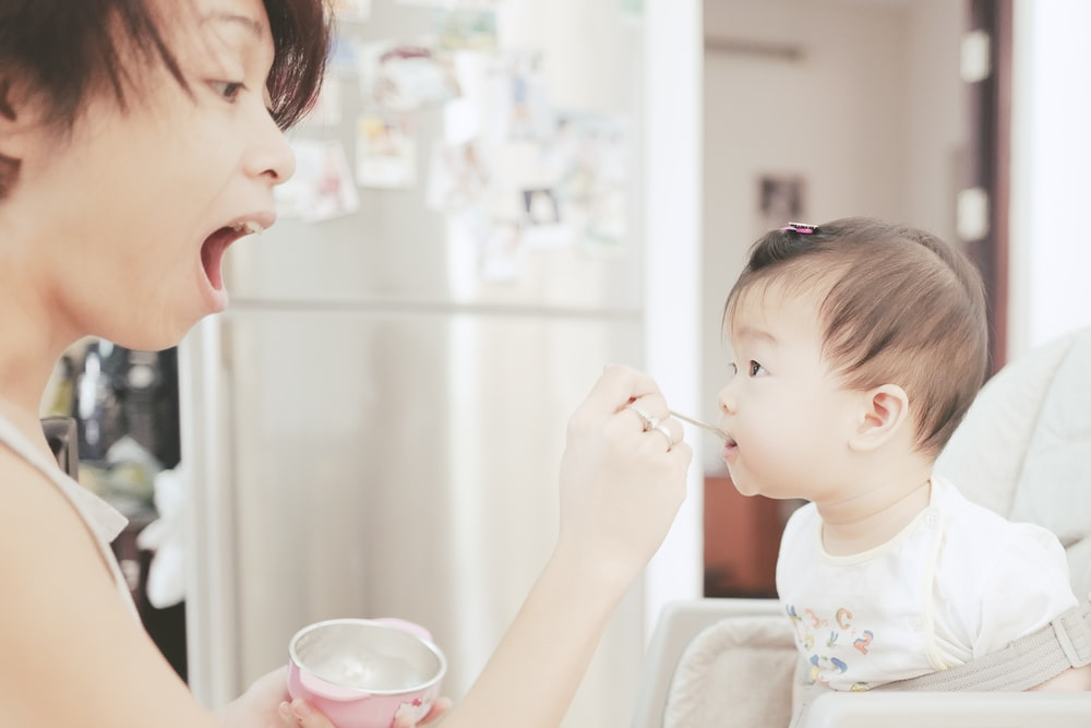 mother feeds the baby using small spoon