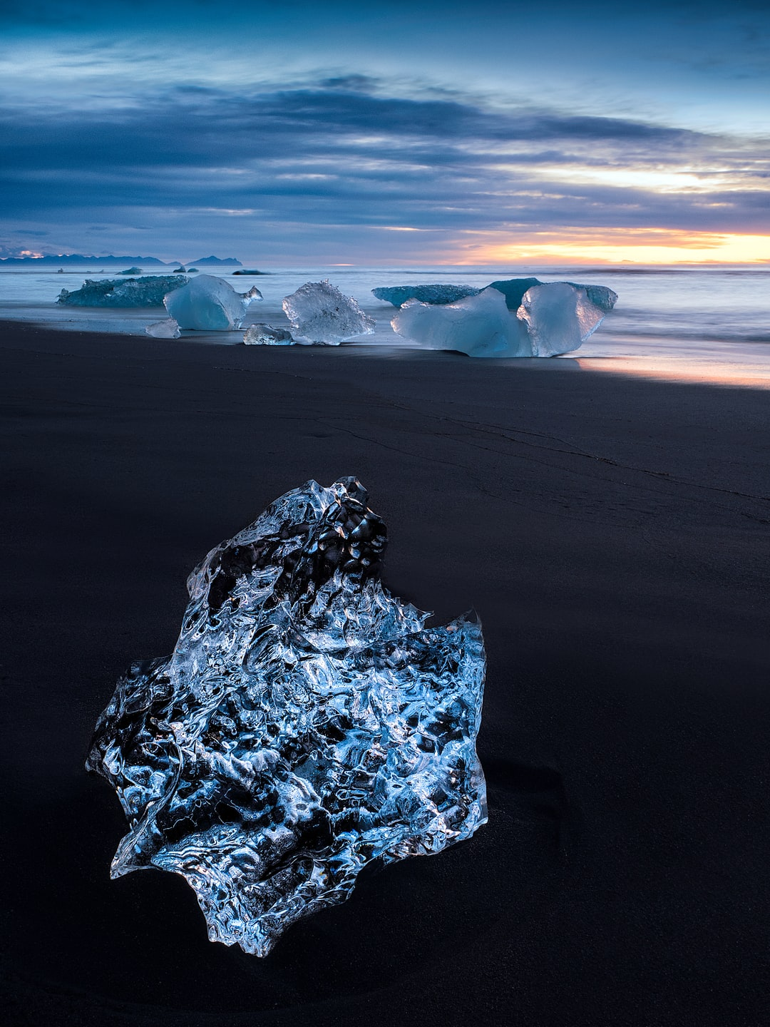 A crystal clear iceberg washed up on the black volcanic sands of the beach at Jökulsárlón, Iceland (Glacier Lagoon). This image was shot at sunrise.