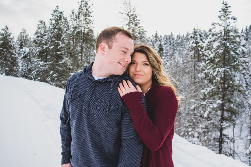 man and woman hugging on top of snow mountain