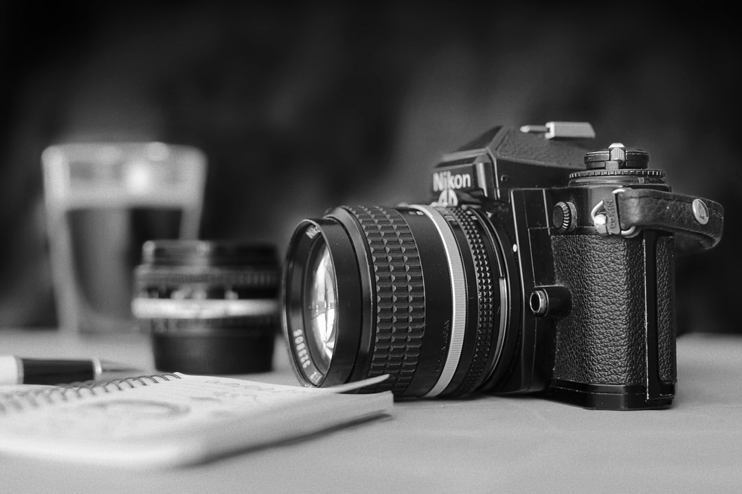 A monochrome scene about the photographer's life: a notebook to write and draw the ideas and the processes, the camera and a choice of precious lenses, and a hot coffee of course!
