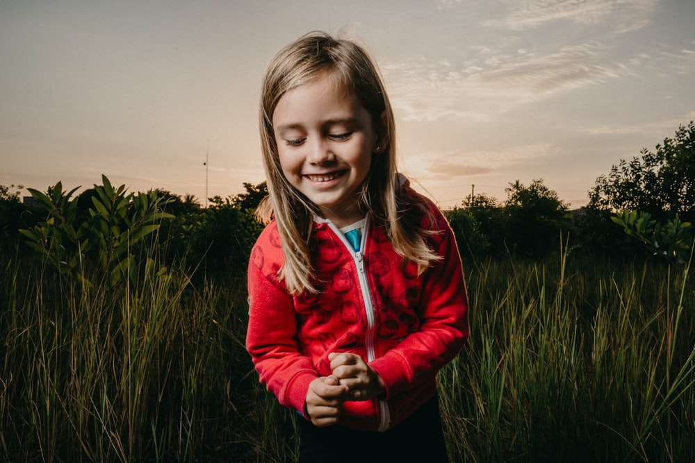 girl wearing red zip-up jacket standing on green grass