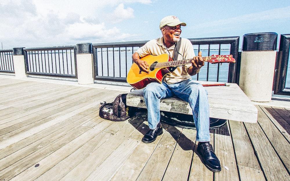 man sitting on bench while playing guitar