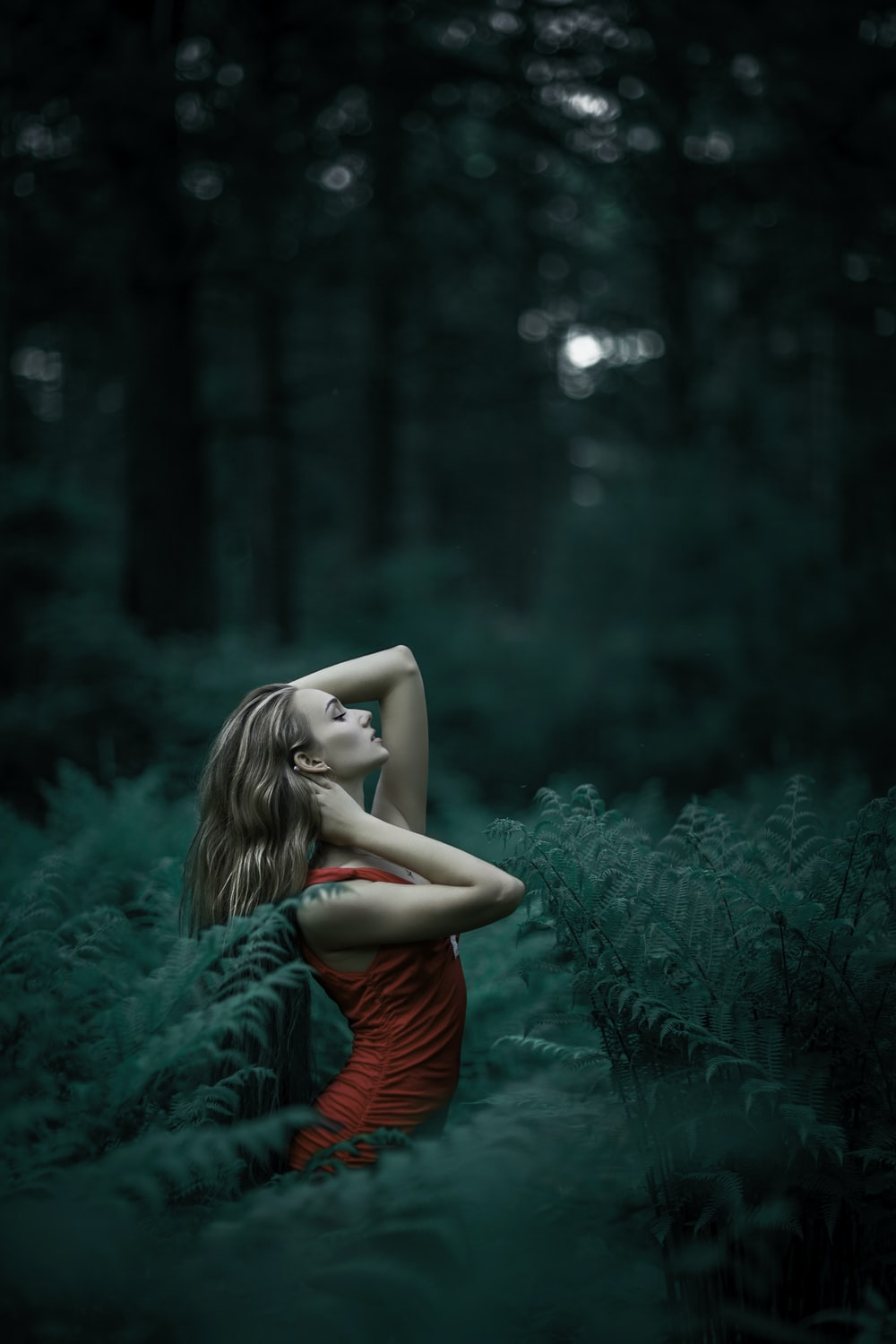 woman standing in the middle of forest
