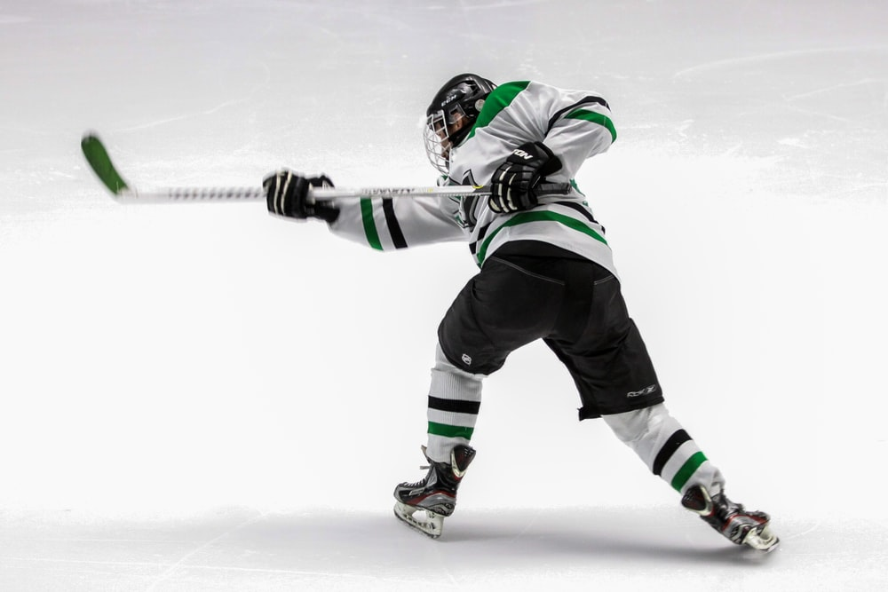 man wearing green and white ice hockey jersey while playing