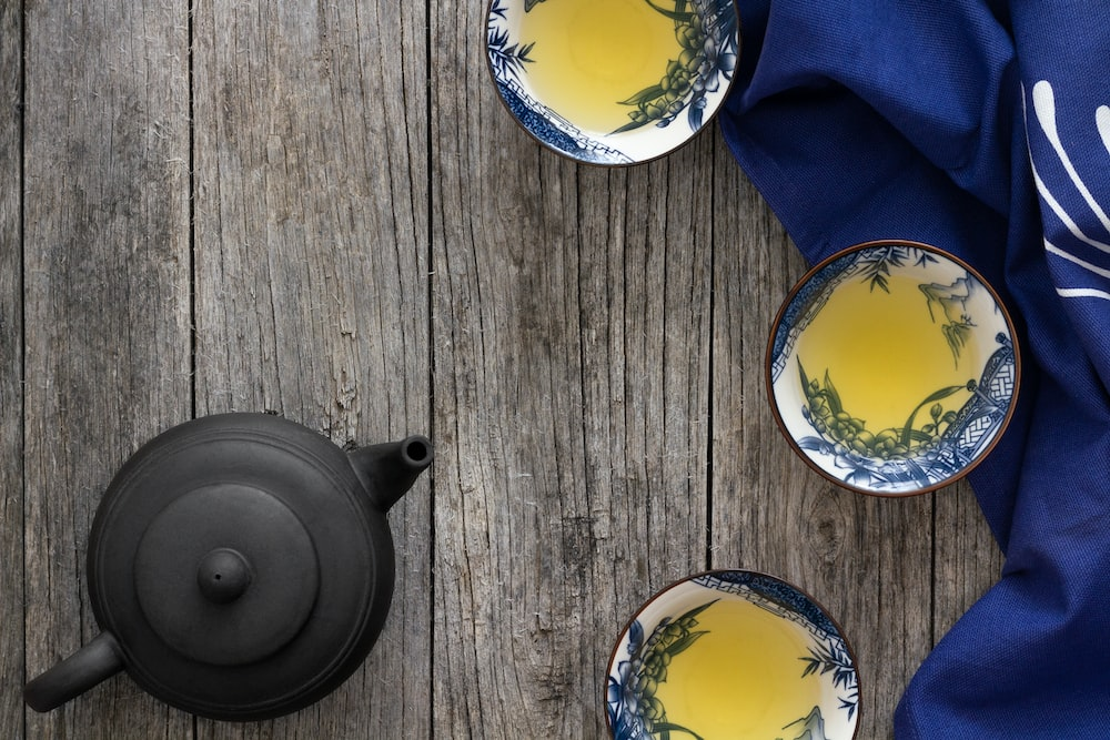 black teapot and three white cups