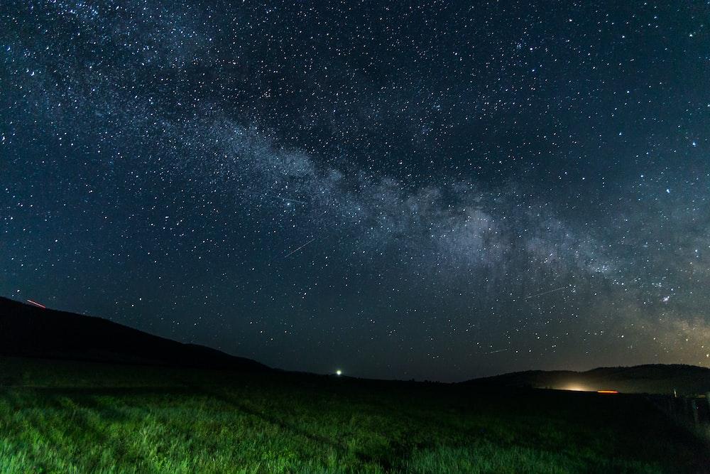 green field under starry sky