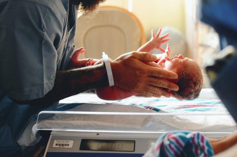 灰色のシャツを着て赤ちゃんを体重計に乗せている人