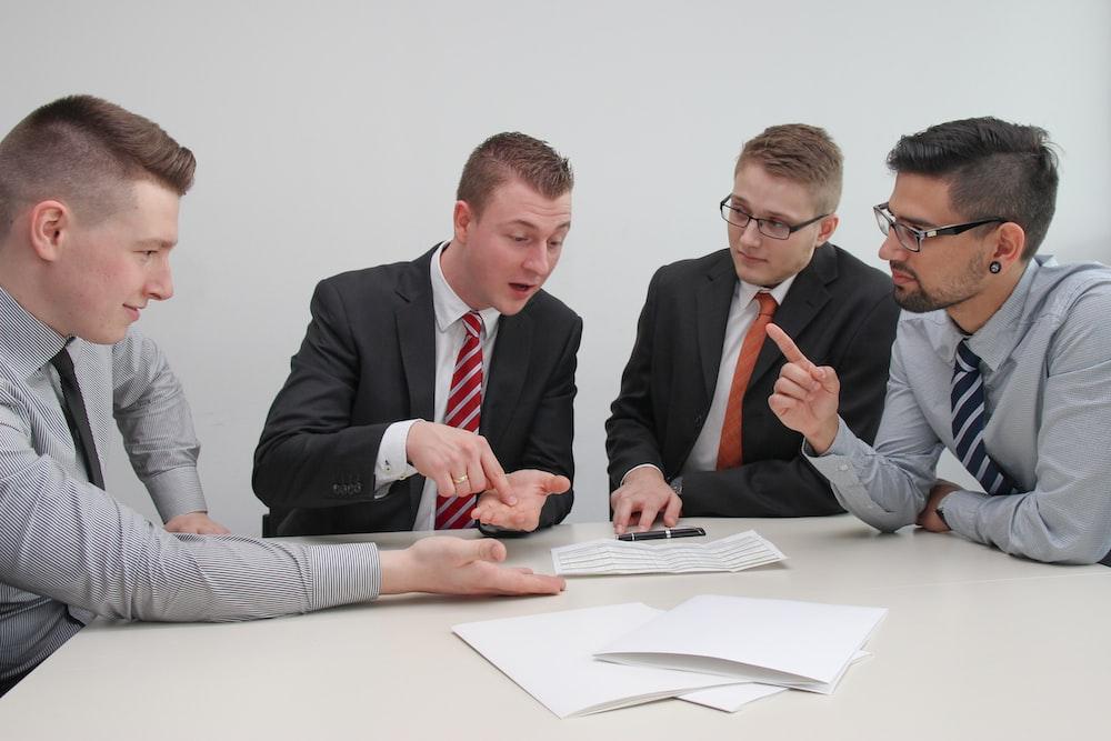 four men sitting at desk talking