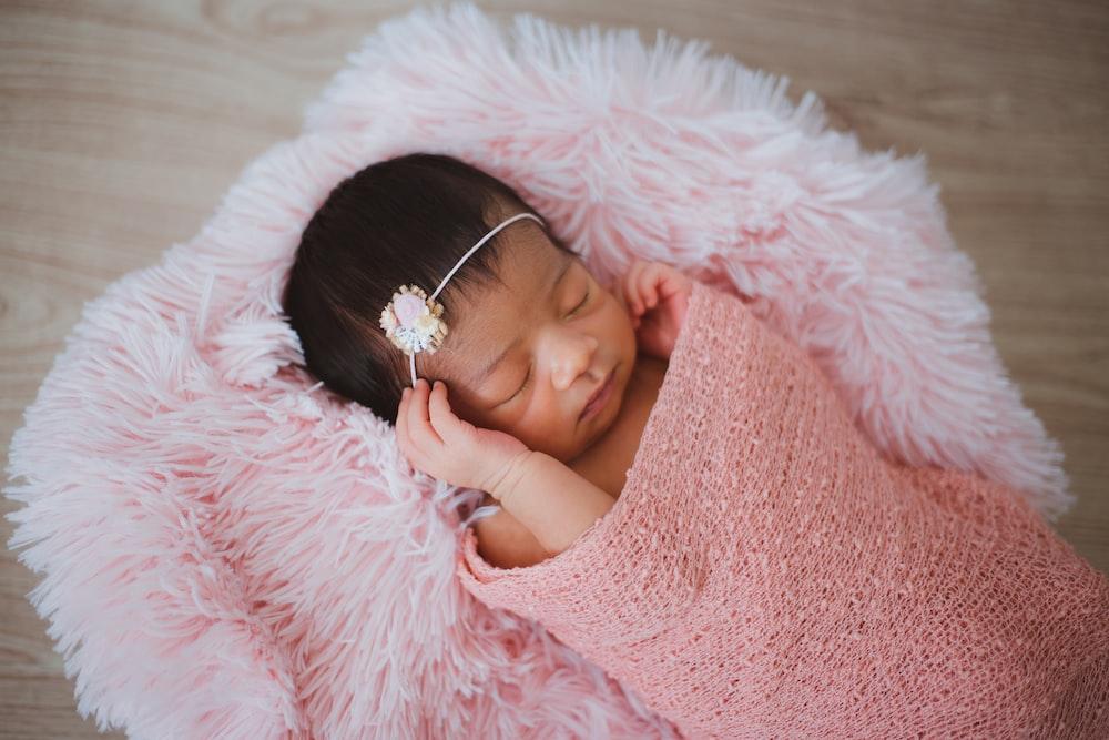 baby sleeping on pink fur pad