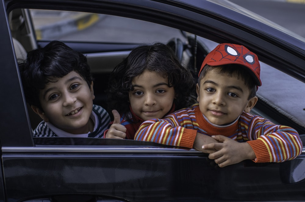 three boys looking outside window of car front seat