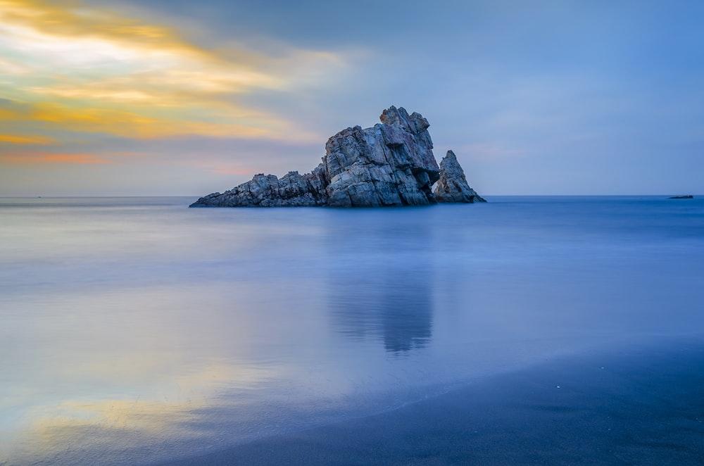 body of water across gray rock
