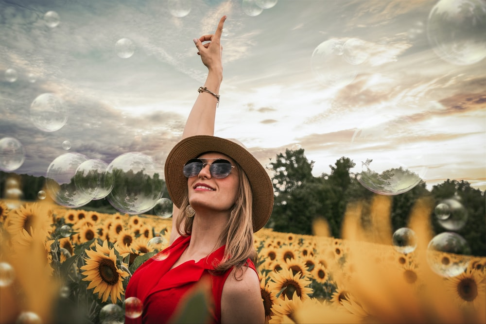 woman in red top lifting hand on middle of sunflower field