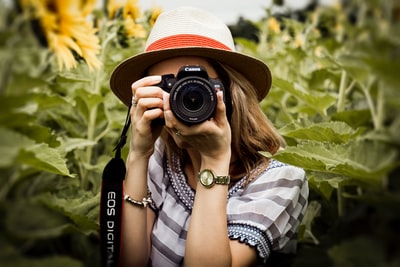 woman taking photo of plants photographer zoom background