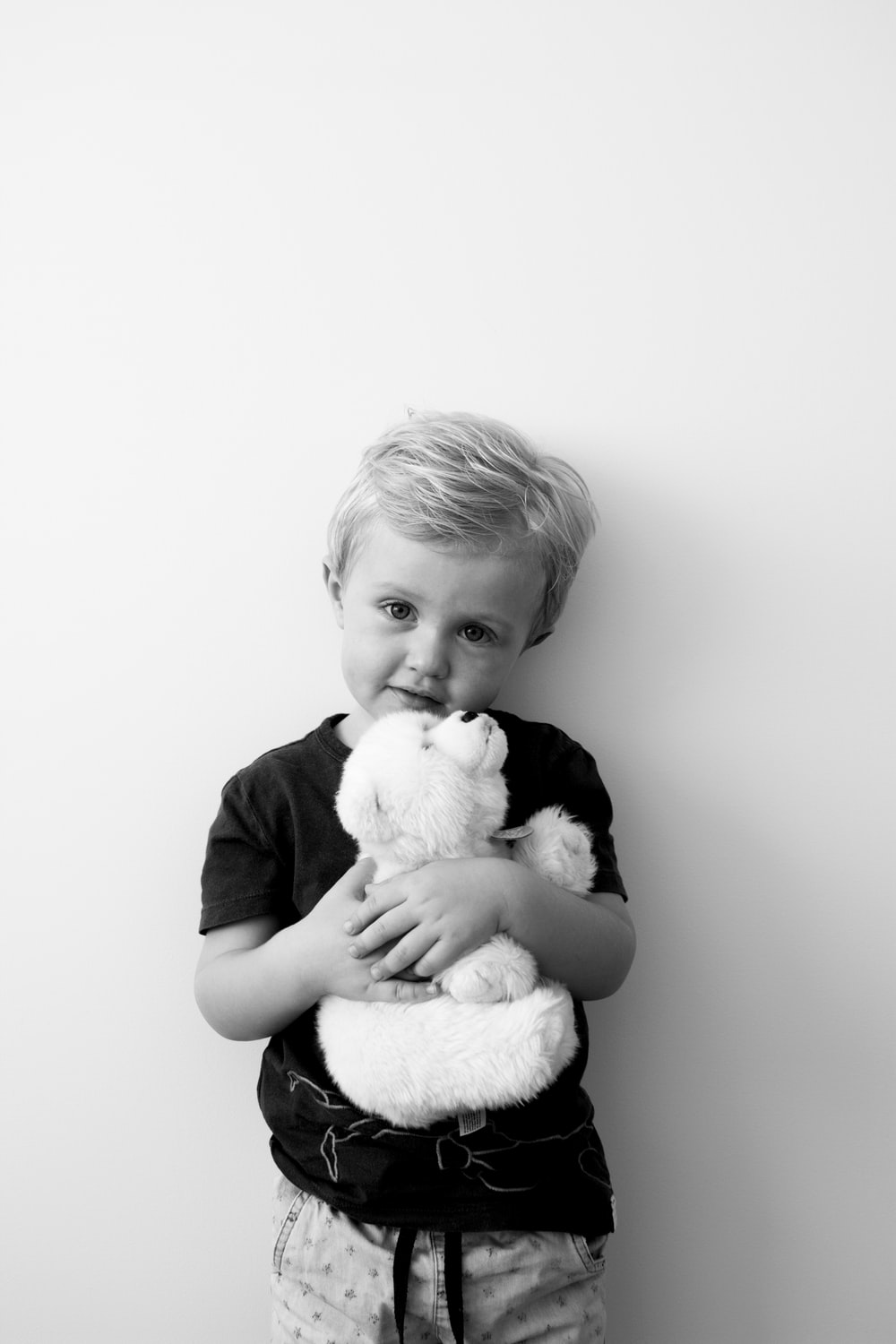 grayscale photography of boy holding bear plush toy