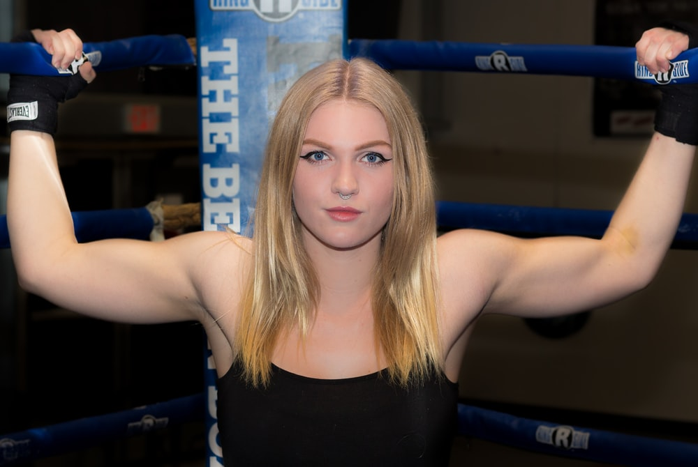 woman gripping boxing rink with both hand