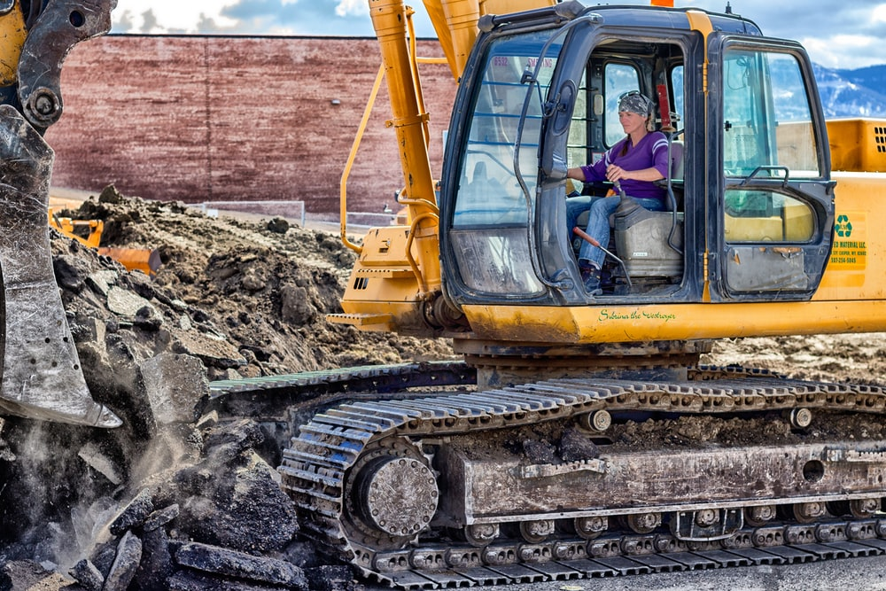 woman riding on yellow excavator at daytime
