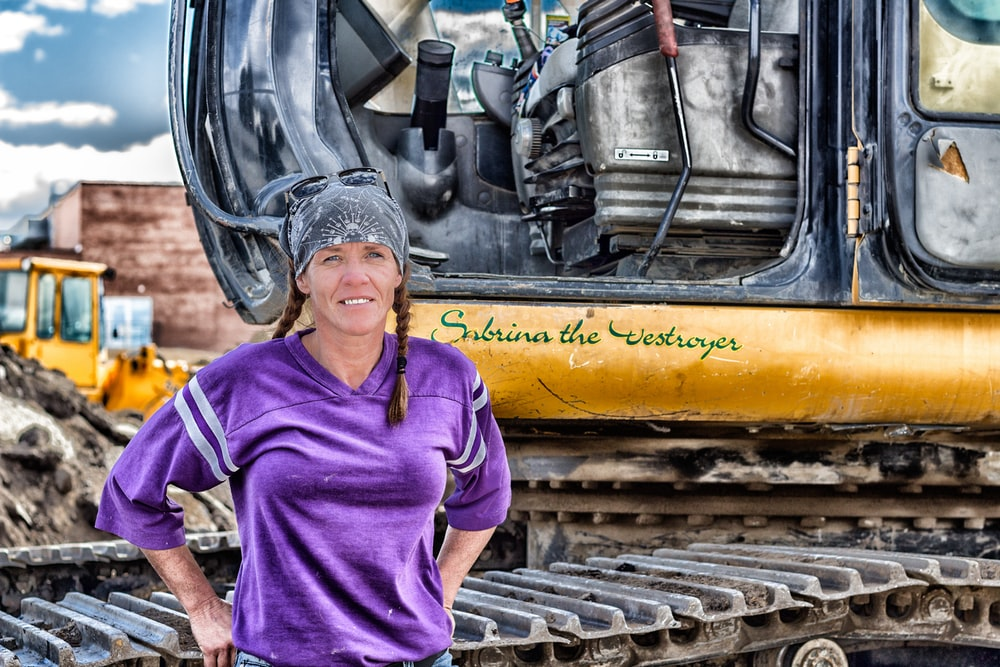 woman standing next to construction vehicle