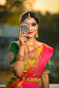woman in green, gold, and red sari dress hiding her right eye while smiling