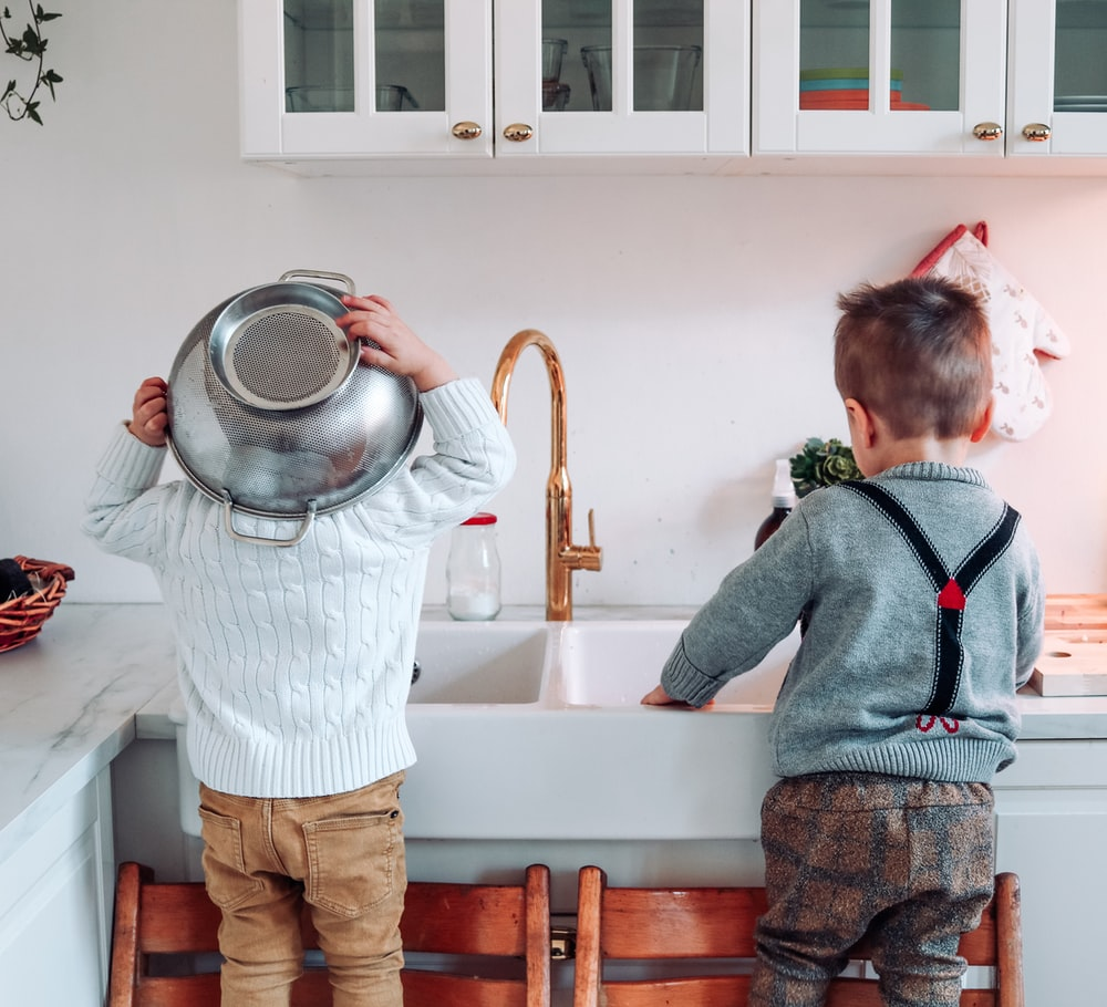 two boys standing on chair near sink