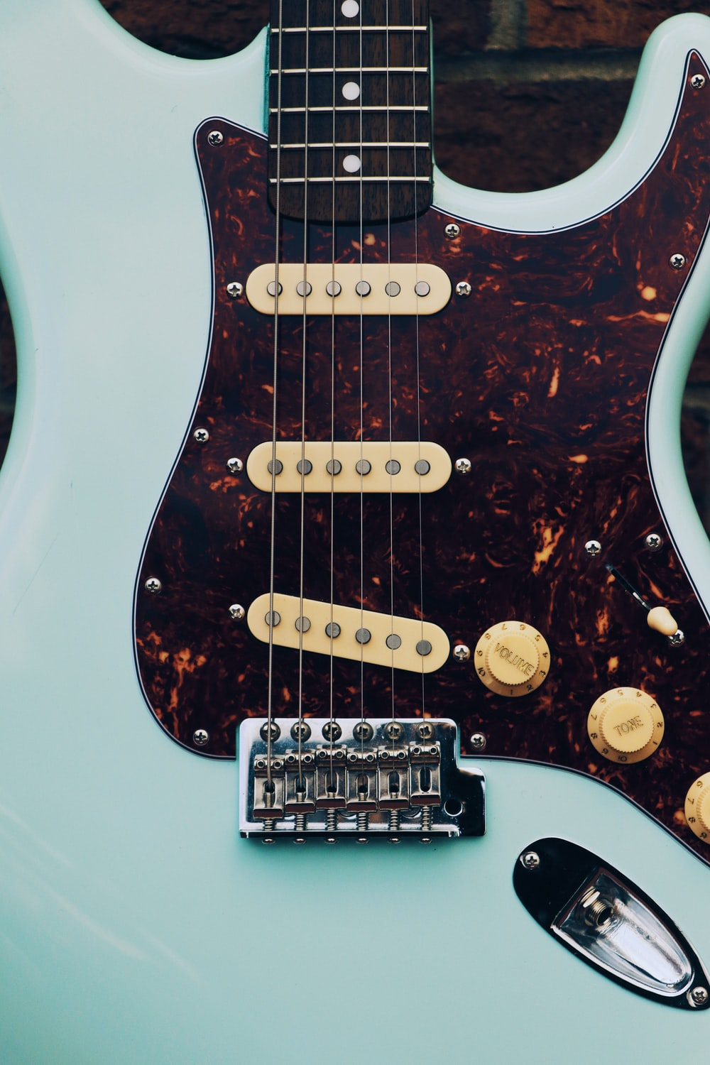white and brown electric guitar