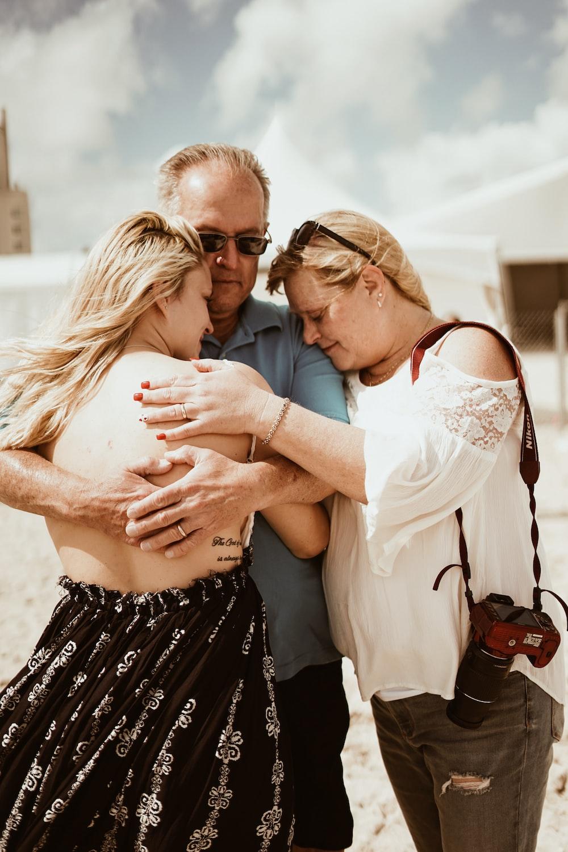 man hugging woman beside woman during daytime