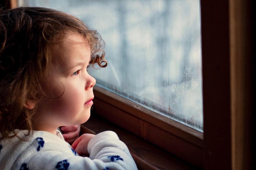 girl standing near window panel