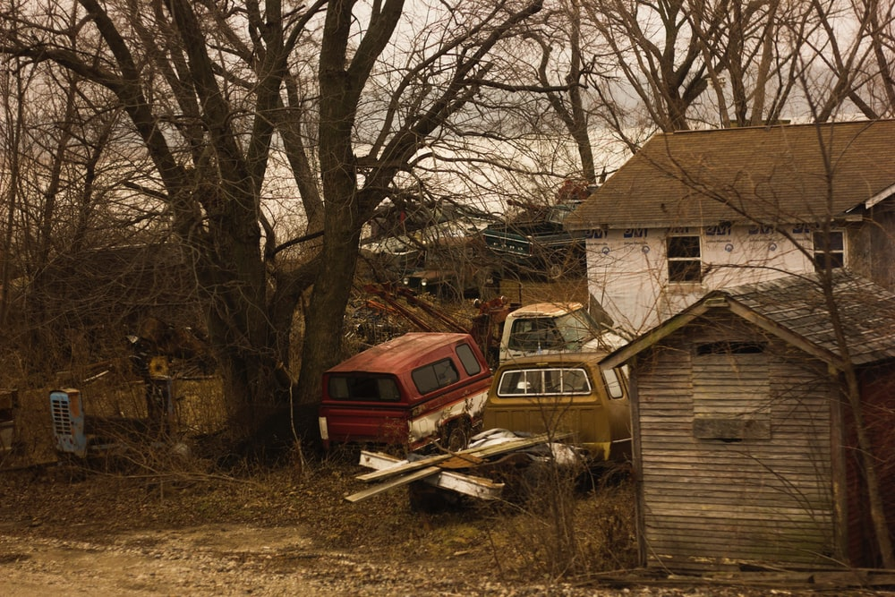 abandoned vehicles in front of house under the trees