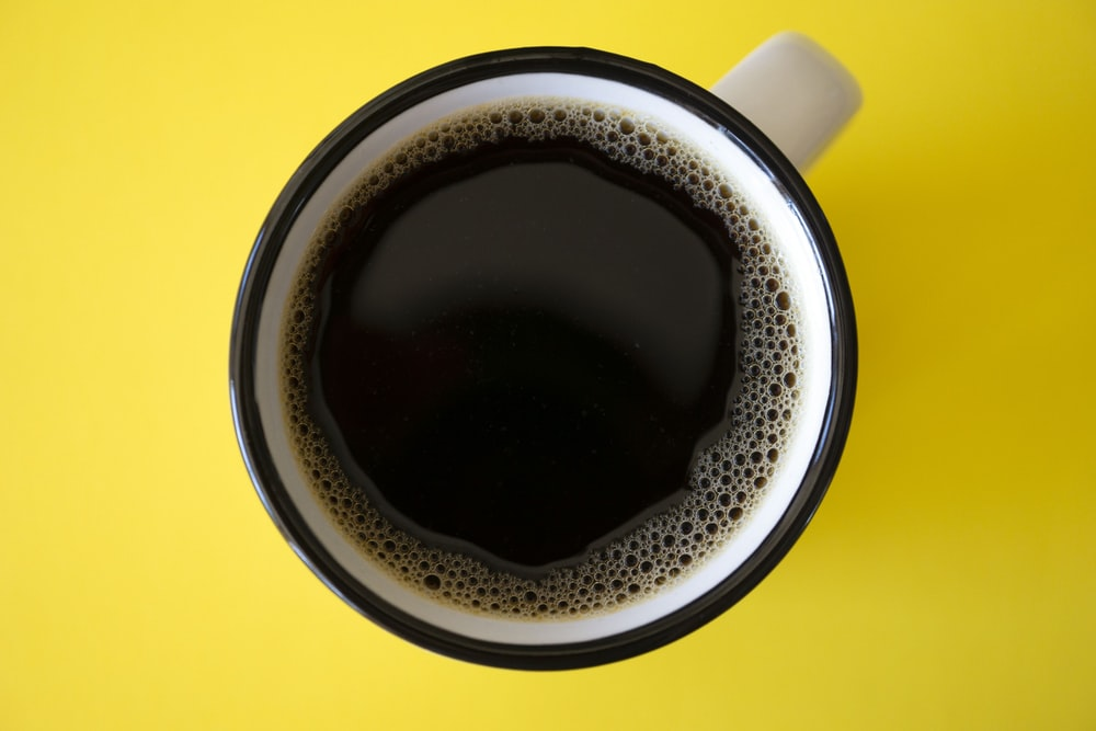 cup of black coffee on yellow surface