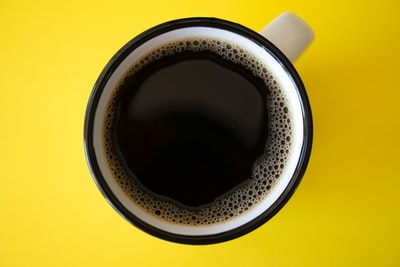 cup of black coffee on yellow surface cup zoom background